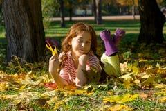 Ένα κοκκινομάλλες κορίτσι στις λαστιχένιες μπότες βρίσκεται στα κίτρινα φύλλα στο τ Στοκ εικόνες με δικαίωμα ελεύθερης χρήσης