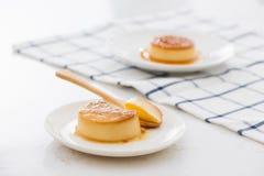 Ένα κομμάτι δαγκωμάτων της γλυκιάς κρεμώδους κρέμας καραμέλας στο κουτάλι και στο πιάτο στοκ εικόνες