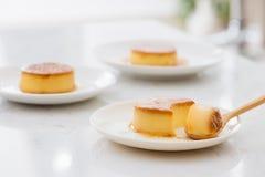 Ένα κομμάτι δαγκωμάτων της γλυκιάς κρεμώδους κρέμας καραμέλας στο κουτάλι και στο πιάτο στοκ φωτογραφία με δικαίωμα ελεύθερης χρήσης