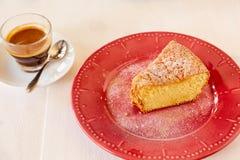 Ένα κομμάτι της εύγευστης πίτας καρότων σε ένα κόκκινο λαμπρό πιάτο Μέρος ενός σπιτικού cupcake σε ένα πιάτο με το μαύρο καφέ Σπι Στοκ Φωτογραφίες