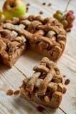 Ένα κομμάτι της σπιτικής πίτας μήλων και των καφετιών σταφίδων στο ελαφρύ ξύλινο υπόβαθρο Η πίτα μήλων που διακοσμείται με τα φρέ Στοκ φωτογραφία με δικαίωμα ελεύθερης χρήσης