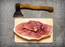 Ένα κομμάτι του ακατέργαστου χοιρινού κρέατος με ένα τσεκούρι για την κοπή κρέατος Στοκ φωτογραφία με δικαίωμα ελεύθερης χρήσης