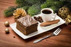 Ένα κομμάτι του κέικ μελοψωμάτων Χριστουγέννων στο άσπρο πιάτο στον εορταστικό πίνακα Στοκ Φωτογραφίες