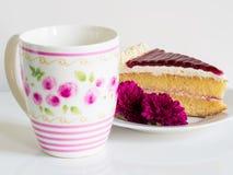 Ένα κομμάτι του κέικ με την όμορφη κούπα και η βιολέτα ανθίζουν Στοκ φωτογραφία με δικαίωμα ελεύθερης χρήσης