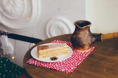 Ένα κομμάτι του κέικ στο πιάτο και του καφέ στον πίνακα στοκ εικόνα