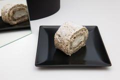 Ένα κομμάτι του ρόλου ξύλων καρυδιάς με την κτυπημένη κρέμα σε ένα μαύρο πιάτο Στοκ εικόνες με δικαίωμα ελεύθερης χρήσης