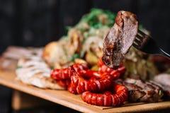 Ένα κομμάτι του ψημένου στη σχάρα κρέατος στο δίκρανο μπροστά από το ψημένο σύνολο κρέατος επάνω Στοκ Εικόνες