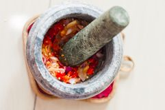 Ένα κονίαμα και ένα γουδοχέρι ή lesung batu σε της Μαλαισίας με τα συντριμμένα τσίλι, τα τηγανισμένες κρεμμύδια και την κόλλα γαρ στοκ φωτογραφία με δικαίωμα ελεύθερης χρήσης