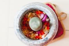 Ένα κονίαμα και ένα γουδοχέρι ή lesung batu σε της Μαλαισίας με τα συντριμμένα τσίλι, τα τηγανισμένες κρεμμύδια και την κόλλα γαρ στοκ εικόνες