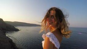 Ένα κορίτσι δίπλα στη θάλασσα και τις στροφές στη κάμερα και από χαμογελά - είναι στο λόφο και υπάρχει ηλιοβασίλεμα απόθεμα βίντεο