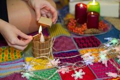 Ένα κορίτσι ανάβει ένα κερί κοντά σε ένα χριστουγεννιάτικο δέντρο Στοκ φωτογραφία με δικαίωμα ελεύθερης χρήσης