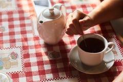 Ένα κορίτσι ανακατώνει τη ζάχαρη σε ένα φλυτζάνι με το τσάι Φλυτζάνι του τσαγιού στον πίνακα Ένα φλυτζάνι του πρόσφατα παρασκευασ στοκ φωτογραφία