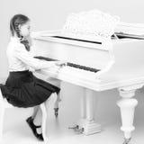 Ένα κορίτσι από ένα σχολείο μουσικής παίζει το πιάνο Στοκ Εικόνες