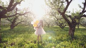 Ένα κορίτσι δέκα ετών που παίζουν με τα μπαλόνια σε έναν οπωρώνα μήλων φιλμ μικρού μήκους