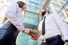 Ένα κορίτσι δίνει ένα άτομο στα χέρια των χρημάτων στο υπόβαθρο ενός κτιρίου γραφείων Πληρωμή για τις υπηρεσίες Μισθός στο φάκελο στοκ φωτογραφία με δικαίωμα ελεύθερης χρήσης