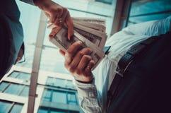 Ένα κορίτσι δίνει ένα άτομο στα χέρια των χρημάτων στο υπόβαθρο στοκ εικόνες
