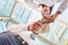 Ένα κορίτσι δίνει ένα άτομο στα χέρια των χρημάτων στο υπόβαθρο στοκ φωτογραφίες με δικαίωμα ελεύθερης χρήσης