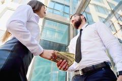 Ένα κορίτσι δίνει ένα άτομο στα χέρια των χρημάτων στο υπόβαθρο στοκ φωτογραφίες