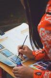 Ένα κορίτσι εφήβων χρωματίζει μια εικόνα με τα watercolors απεικόνιση αποθεμάτων