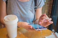 Ένα κορίτσι κάθεται με ένα τηλέφωνο σε έναν καφέ Στοκ Εικόνες