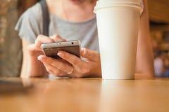 Ένα κορίτσι κάθεται με ένα τηλέφωνο σε έναν καφέ Στοκ Φωτογραφίες