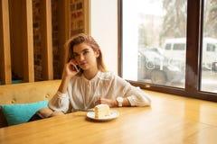 Ένα κορίτσι κάθεται σε έναν καφέ και χρησιμοποιεί ένα smartphone Στοκ Εικόνες