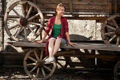 Ένα κορίτσι κάθεται σε ένα παλαιό telega στοκ εικόνες