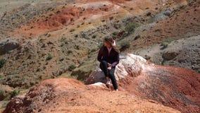 Ένα κορίτσι κάθεται σε ένα βουνό στο υπόβαθρο των εγκαταλειμμένων λόφων απόθεμα βίντεο