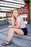 Ένα κορίτσι κάθεται στα σκαλοπάτια μιλώντας στο τηλέφωνο Στοκ Φωτογραφίες