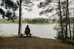 Ένα κορίτσι κάθεται στην άκρη του απότομου βράχου σε μια καρέκλα και τα δέντρα στοκ φωτογραφία