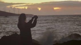 Ένα κορίτσι κάνει μια φωτογραφία ηλιοβασιλέματος θάλασσας χρησιμοποιώντας μια κινητή συσκευή απόθεμα βίντεο