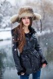 Ένα κορίτσι κάτω από το χιόνι σε μια ΚΑΠ με τα earflaps Στοκ Εικόνες
