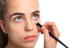 Ένα κορίτσι καθαρίζεται με τους μώλωπες κάτω από τα μάτια της σε ένα απομονωμένο λευκό υπόβαθρο στοκ εικόνες