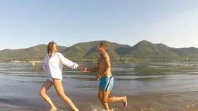 Ένα κορίτσι και ένας τύπος που τρέχουν γύρω στην παραλία φιλμ μικρού μήκους