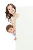 Ένα κορίτσι και ένα αγόρι κοιτάζουν έξω από πίσω από τον τοίχο στοκ εικόνα με δικαίωμα ελεύθερης χρήσης