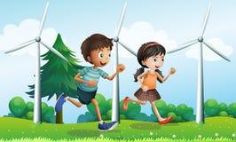 Ένα κορίτσι και ένα αγόρι που τρέχουν στο λόφο με τους ανεμόμυλους Στοκ Φωτογραφίες