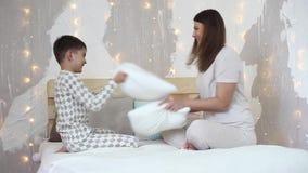 Ένα κορίτσι και ένα μικρό αγόρι έχουν τη διασκέδαση που χτυπά η μια την άλλη με τα κουπιά που κάθονται στο κρεβάτι HD απόθεμα βίντεο