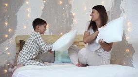 Ένα κορίτσι και ένα μικρό αγόρι έχουν τη διασκέδαση που χτυπά η μια την άλλη με τα κουπιά που κάθονται στο κρεβάτι απόθεμα βίντεο