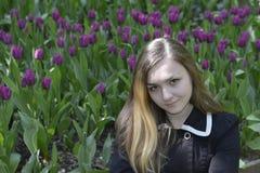 Ένα κορίτσι και πορφυρές τουλίπες Στοκ Εικόνα