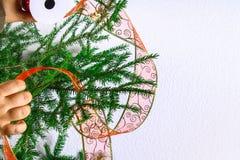 Ένα κορίτσι κρεμά μια κορδέλλα Χριστουγέννων από το organza σε ένα χριστουγεννιάτικο δέντρο σε ένα άσπρο υπόβαθρο Στοκ φωτογραφία με δικαίωμα ελεύθερης χρήσης