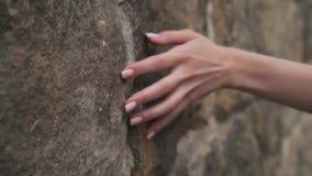 Ένα κορίτσι κτυπά το χέρι της σε έναν τοίχο πετρών απόθεμα βίντεο