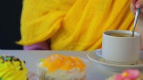 Ένα κορίτσι μετακινεί με το κουτάλι το τσάι σε ένα φλυτζάνι στον πίνακα με τα κέικ απόθεμα βίντεο