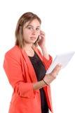 Ένα κορίτσι με ένα κόκκινο σακάκι κρατά μια ψηφιακά ταμπλέτα και ένα τηλέφωνο Στοκ Εικόνες