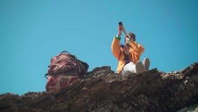 Ένα κορίτσι με μακρυμάλλη σε ένα κίτρινο σακάκι και μια γκρίζα ΚΑΠ στέκεται στα βουνά και κοιτάζει μέσω ενός τηλεσκοπίου απόθεμα βίντεο