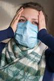 Ένα κορίτσι με μια ιατρική μάσκα στο πρόσωπό της κρατά το κεφάλι της στοκ εικόνα