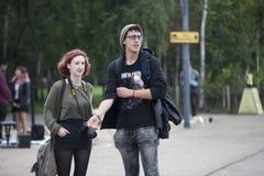 Ένα κορίτσι με μια κάμερα και ένας νεαρός άνδρας με τα γυαλιά ακούνε έναν μουσικό οδών Στοκ Εικόνα