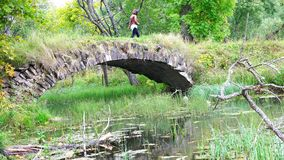 Ένα κορίτσι με μια κάμερα που διασχίζει τον ποταμό σε μια γέφυρα πετρών απόθεμα βίντεο