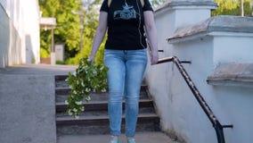 Ένα κορίτσι με μια όμορφη ανθοδέσμη στο χέρι του κάτω από τα σκαλοπάτια Όμορφο σχέδιο στην κίνηση Περίπατος μέσω της πόλης βραδιο απόθεμα βίντεο