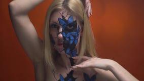 Ένα κορίτσι με στο πρόσωπο και το σώμα της που κτυπιούνται ήπια με τα χέρια της απόθεμα βίντεο
