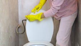 Ένα κορίτσι με τα κίτρινα λαστιχένια γάντια καθαρίζει το καπάκι τουαλετών με ένα σφουγγάρι απόθεμα βίντεο
